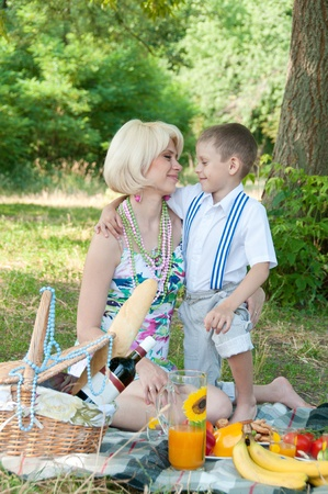 Happy family on a picnic  The son embraces mother  photo