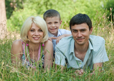 Portrait of happy family lying down on grass  photo