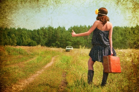 Beautiful brunette with a suitcase in the countryside  Photos in the old style  Banco de Imagens
