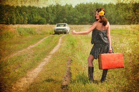 Beautiful brunette with a suitcase in the countryside  Photos in the old style  Stockfoto