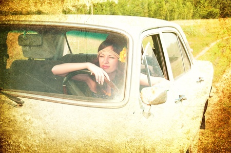 Beautiful brunette with flower in her hair sitting behind the wheel of an old car  Photos in the old style