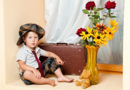 Cute little boy with the flower. He is wearing a hat.