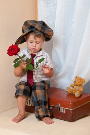 Cute little boy with the flower sitting on an old suitcase. He is wearing a hat.
