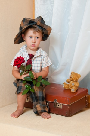 Cute little boy with the flower sitting on an old suitcase. He is wearing a hat. photo