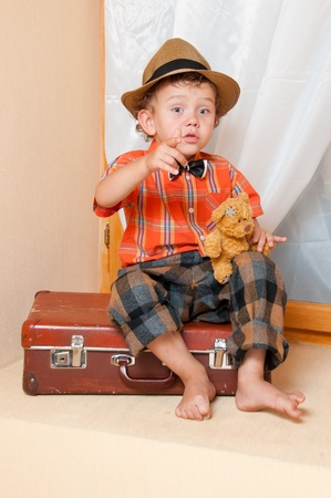 A boy with a teddy bear sitting on a suitcase. Stock Photo - 13181884