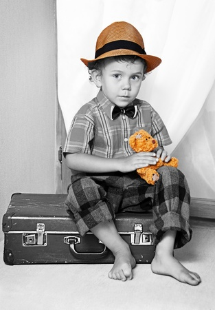 portmanteau: A boy with a teddy bear sitting on a suitcase. Stock Photo