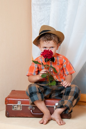 Cute little boy with the flower sitting on an old suitcase. He is wearing a hat. Stock Photo - 13181915