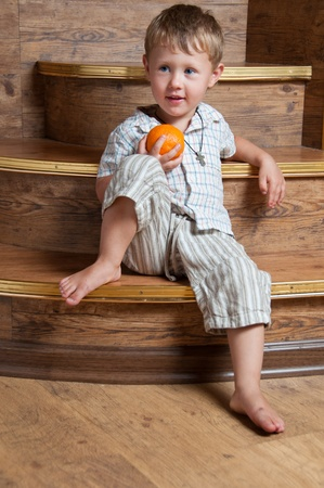 A cute boy with an orange in his hand sitting on the steps. photo