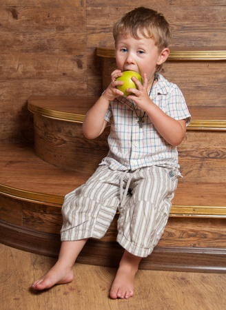 A cute boy with an apple in his hand sitting on the steps. Stock Photo - 13181907