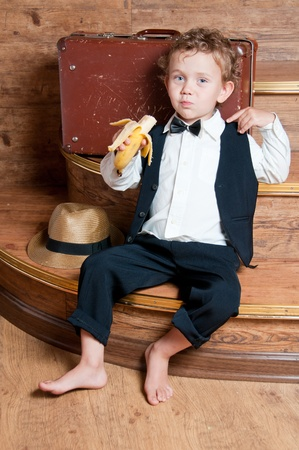 Cute little boy with a banana in his hand sitting on the steps  Photo of retro style Stock Photo - 13181971