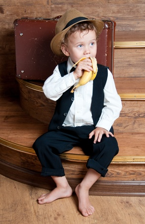 Cute little boy with a banana in his hand sitting on the steps  Photo of retro style