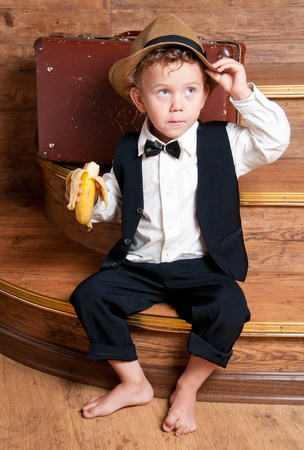 Cute little boy with a banana in his hand sitting on the steps  Photo of retro style Stock Photo - 13181933