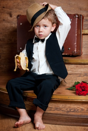 Cute little boy with a banana in his hand sitting on the steps  Photo of retro style Stock Photo - 13181898