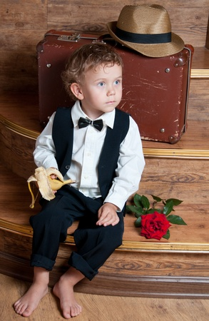 Cute little boy with a banana in his hand sitting on the steps  Photo of retro style  Stock Photo - 13181921