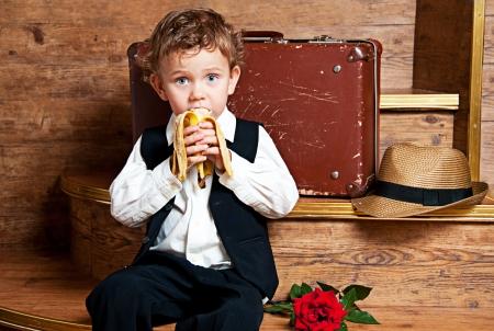 Cute little boy con un plátano en la mano sentado en el Foto medidas de estilo retro Foto de archivo - 13181985