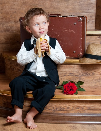 Cute little boy with a banana in his hand sitting on the steps  Photo of retro style Stock Photo - 13181882