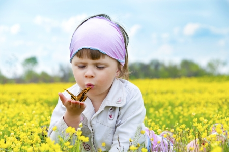 Little cute girl in a field of beautiful yellow flowers holding a butterfly on the palms and blowing on it