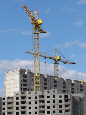 apartment shortage: High-rise buildings under construction in progress  Construction cranes and unfinished building under a blue cloudy sky