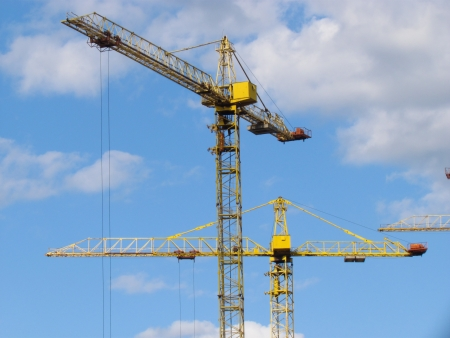 High-rise buildings under construction in progress  Construction cranes and unfinished building under a blue cloudy sky