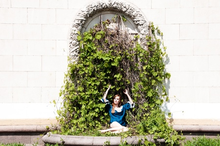 A beautiful red-haired girl sits in the arch of green creepers  photo