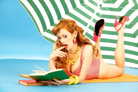 sexy woman reading book by the sea