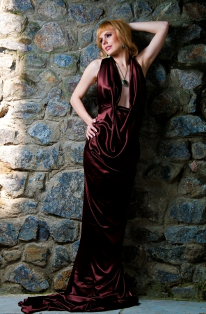 Beautiful blonde girl in evening dress, posing against a stone wall Stock Photo