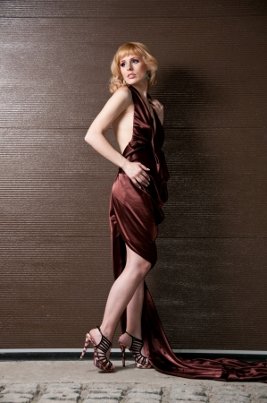 coquetry: Pretty confident blonde girl in evening dress, posing against a brown wall Stock Photo