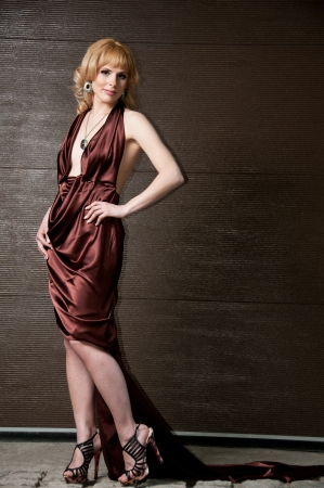 Pretty confident blonde girl in evening dress, posing against a brown wall photo