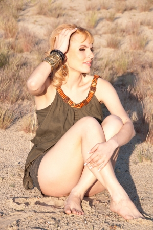 coquetry: Beautiful blonde in a khaki shirt, sitting on the sand  Unbearable heat