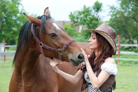 Beautiful brunette girl stroking a horse