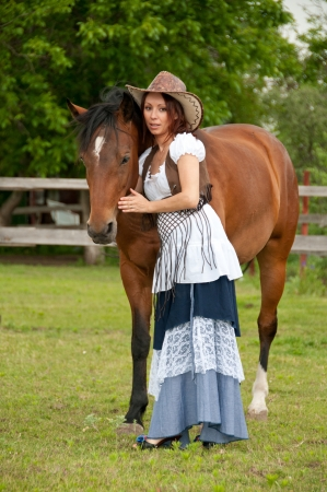 cute young farm girl: A beautiful  girl in a cowboy hat with a horse
