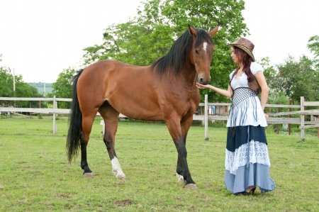 brown haired: A beautiful  girl in a cowboy hat with a horse