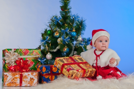 Charming baby  girl  in Santa Claus suit, with Christmas tree and gifts