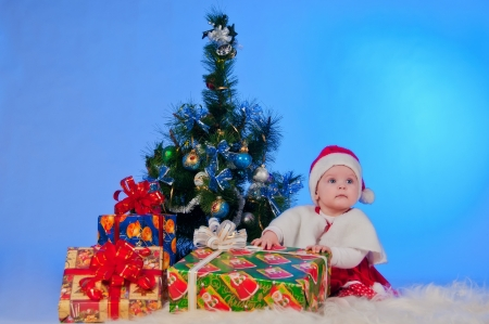 Charming baby  girl  in Santa Claus suit, with Christmas tree and gifts photo