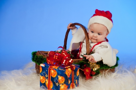 Baby Santa  Cute little girl dressed as Santa Claus sitting in a wicker basket with a gift  Basket decorated Christmas tree bells photo