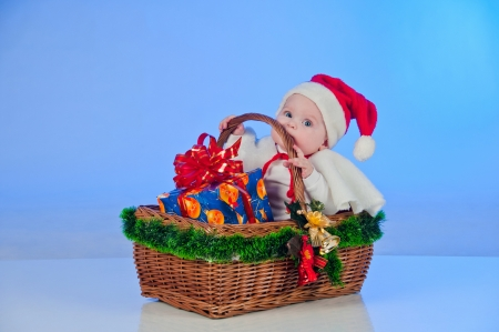 Baby Santa  Cute little girl dressed as Santa Claus sitting in a wicker basket with a gift  Basket decorated Christmas tree bells Stock Photo - 15489129