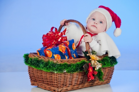 Baby Santa  Cute little girl dressed as Santa Claus sitting in a wicker basket with a gift  Basket decorated Christmas tree bells Stock Photo - 15489137