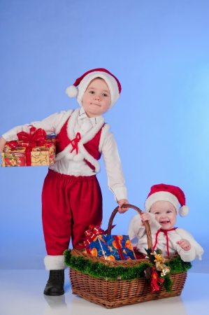 Happy New year  Charming Santa helpers  Little boy and a girl dressed as Santa bring Christmas gifts in a wicker basket Stock Photo - 15489113