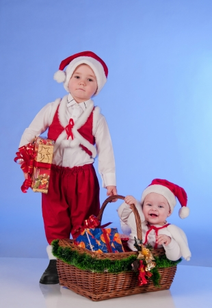 Happy New year  Charming Santa helpers  Little boy and a girl dressed as Santa bring Christmas gifts in a wicker basket Stock Photo - 15489104
