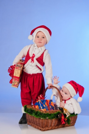 Happy New year  Charming Santa helpers  Little boy and a girl dressed as Santa bring Christmas gifts in a wicker basket Stock Photo - 15489103