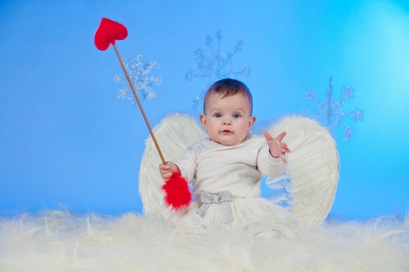 Cute smiling Christmas angel baby with angel wings and Cupid photo