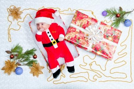 Charming newborn baby boy in Santa Claus suit photo