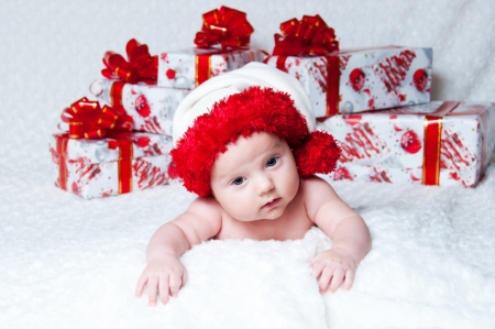 Newborn baby boy Santa Claus with Christmas gifts photo