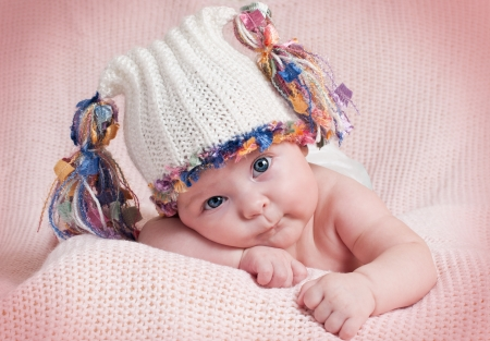 The little girl in hat lying on his tummy and looks   photo