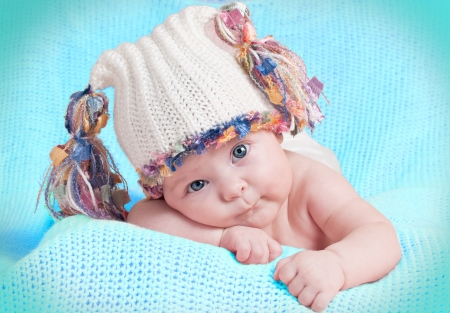 The little girl in hat lying on his tummy and looks   Stock Photo - 15468966