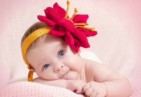lying on his tummy: The little girl in hat lying on his tummy and looks  Stock Photo