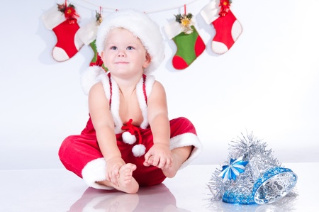 christmas costume: Cute baby Santa Claus with garlands of Christmas bootee Stock Photo