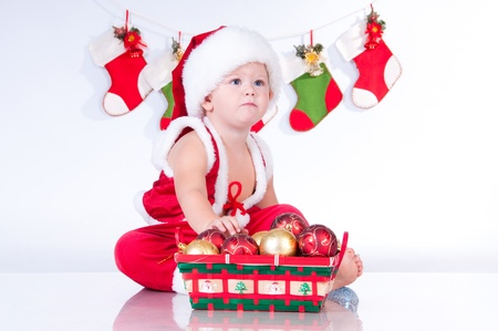 bootee: Cute baby Santa Claus with garlands and a basket of Christmas toys