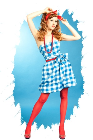 Pretty sexy redhead Pin Up girl in a checkered dress and red stockings adjusts the bow on her head photo