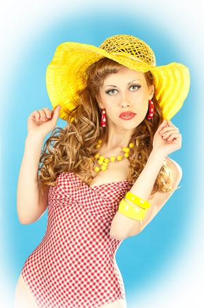 Bright seductive charming pin-up girl in a pink bathing suit and a broad yellow hat Stock Photo